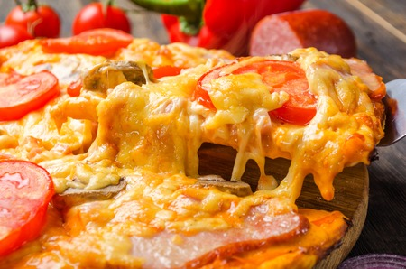 Italian pizza with tomatoes and mushrooms on a wooden board