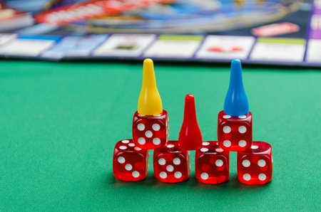 red dice for board games with chips on a green background