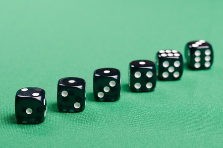black gambling dice for casinos on a green background