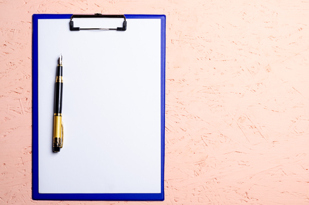 blank paper with pen in folder on wooden table in studio