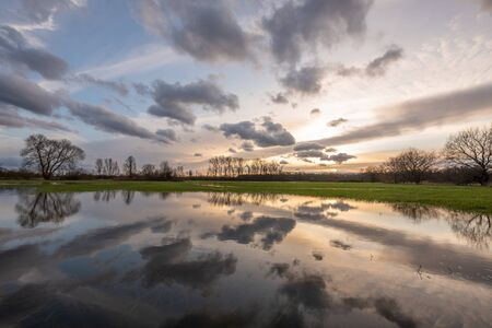 Cloudy sky reflecting in the water in a flooded meadow