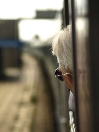 Old man looks outside the train. photo