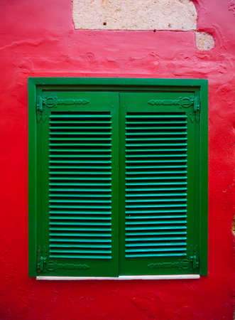 Rustic old green window on a bright red facade of a mediterranean building. Zdjęcie Seryjne