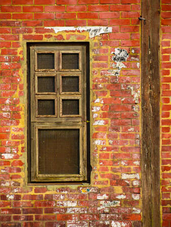 Wooden window in old brick wall with leftovers of glue and ripped paper from posters.
