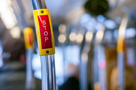 Big red stop button inside a bus with defocused background