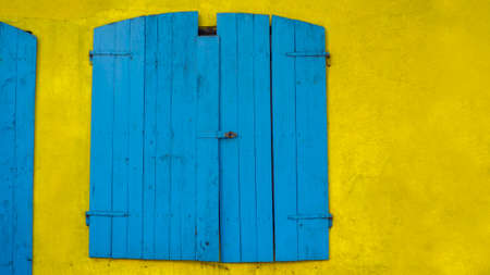 Old blue window made of wood in bright yellow wall