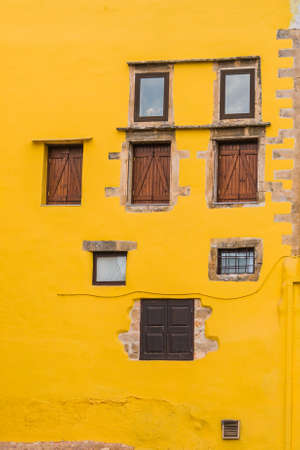 Warm yellow facade with rustic windows in the port of the Mediterranean city of Chania