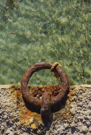 Old rusty metal ring in harbor used for boat anchoring