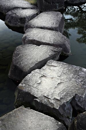 across: Stone path across a tranquil pond Stock Photo