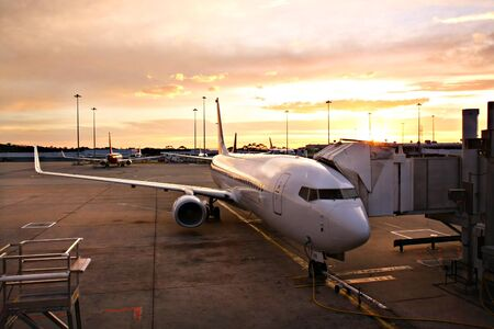 Plane at Melbourne Airport Terminal at Sunrise Stock Photo