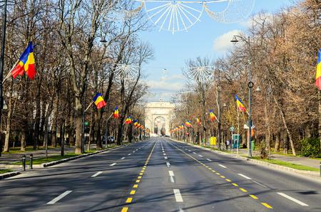 El arco del triunfo (Arcul de Triumf) de Bucarest Rumania, Día Nacional con banderas rumano, vista desde la avenida Kisseleff.