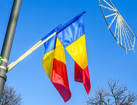 Romanian Flag in the sun, National Day of Romania, blue sky close up. Stock Photo