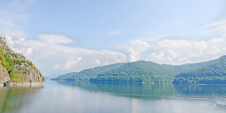 The barrage, dam Vidraru on the river Arges, green hills and rocks, blue sky Stock Photo