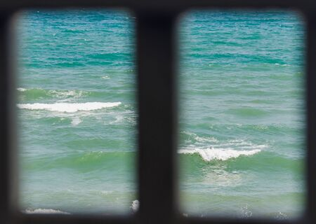 balchik: Frame window with view to blue, green sea water waves, seaside with water foam, close up.