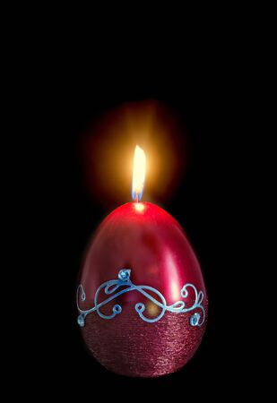 easter candle: Egg shape, oval Easter candle, flame, isolated, close up, dark background. Stock Photo