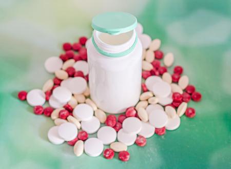 pilule: Píldoras de drogas rojo, blanco, amarillo con blanco botella de plástico abierto, polvo, manojo, médico, homeopáticos, fondo verde, de cerca
