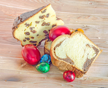 Cakes called Pasca made with cheese and raisins, Cozonac with smashed nuts, traditional colored easter eggs, wood background.