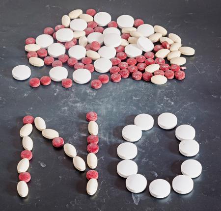 pilule: NO escritura de color rojo, amarillo, drogas blanco píldoras, polvos, manojo, no drogas, gradiente de fondo oscuro, de cerca. Foto de archivo