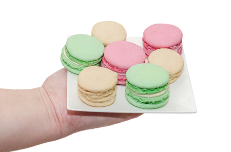 Woman hand holding a white plate with colored sweet macaroons, french traditional, cream, close up, white background
