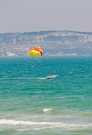 ALBENA, BULGARIA - JUNE 19, 2016. Colored parasail wing pulled by a boat in the blue water sea