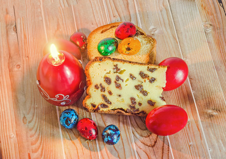 Cakes called Pasca made with cheese and raisins, traditional colored easter eggs, candle, wood background. Stock Photo