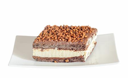 Pastel de chocolate con avellanas y crema blanca, nueces, plato blanco, aislado sobre fondo blanco, de cerca Foto de archivo