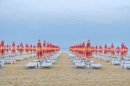 ALBENA, BULGARIA - JUNE 13, 2016. The Black Sea shore. blue sea water, clouds sunset sky, beach sand with umbrellas and sunbeds