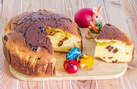 Traditional romanian cake called Pasca with colored easter eggs, bunny, wood background