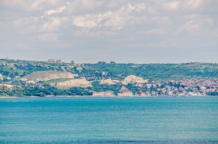 balchik: ALBENA, BULGARIA - JUNE 13, 2016. View of the Black Sea shore, green hills with houses, blue clouds sky. City Balchik coast, blue sea water