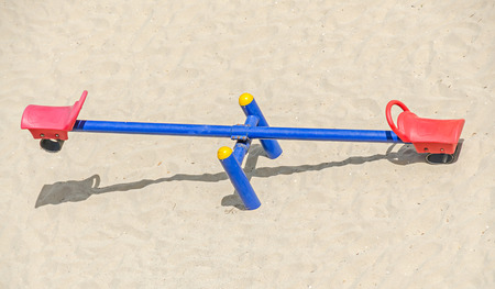 teeter: Teeter totter with red chairs, beach sand, balance, close up, outdoor playground