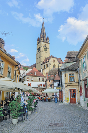 rumanian: SIBIU, ROMANIA - AUGUST 10, 2016: Streets of the downtown city with restaurants and old buildings, Transylvania