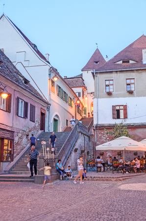 rumanian: SIBIU, ROMANIA - AUGUST 10, 2016: Streets of the downtown city with restaurants and old buildings, Transylvania. Night time
