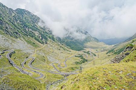 Transfagarasan serpent road from Fagaras mountains, Carpathians with green grass and rocks, clouds fog.