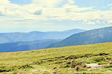 Parang Mountains in the clouds, hills with green grass and rocks, Transalpina road, Carpathian Mountains.