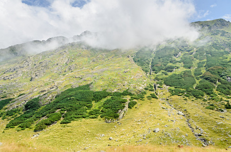 Fagaras mountains, Carpathians with green grass and rocks, peaks in the clouds. Stock Photo