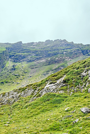 Fagaras mountains, Carpathians with green grass and rocks, clouds fog, Transfagarasan road