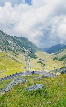 Transfagarasan serpent road from Fagaras mountains, Carpathians with green grass and rocks, clouds fog.