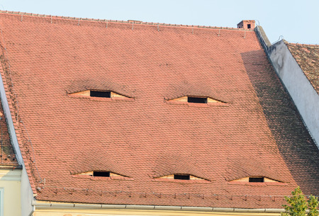 rumanian: SIBIU, ROMANIA - AUGUST 10, 2016: Detail of houses situated near downtown of the city. Roof with eye windows