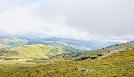 Transalpina road, Parang Mountains, hills with green grass and rocks,  Carpathian Mountains.