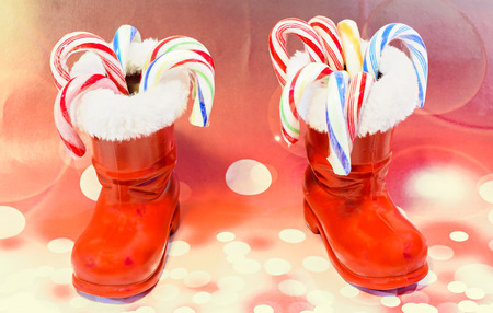 Red Santa Claus boots with candies, lollipops, shoes. Saint Nicholas boots gifts, red lights bokeh background. Stock Photo