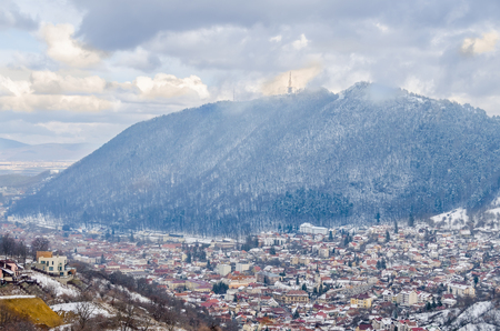 brasov: BRASOV, ROMANIA - MARCH 19, 2015 - The Cityscape of Brasov City in winter time, cloudy day