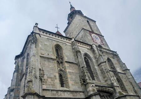 johannes: BRASOV, ROMANIA - MARCH 19, 2015: The church Biserica Neagra (The Black Church) situated near the square Piata Sfatului, and the Statue of Johannes Honterus.