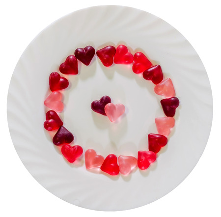 Colored (pink, red and orange), transparent heart shape jellies with ceramic plate, white background, isolated.
