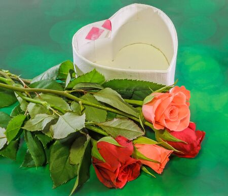 Red and orange roses with heart shape boxe, green wood background