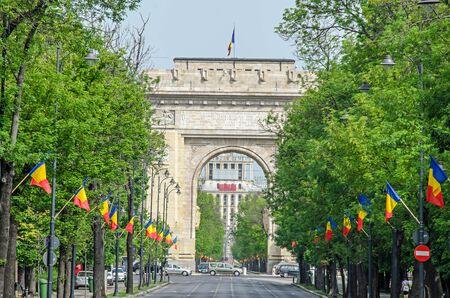 L'arco di trionfo (Arcul de Triumf) da Bucarest Romania, giornata internazionale con bandiere rumene, vista da Kisseleff Avenue. Archivio Fotografico - 77937377