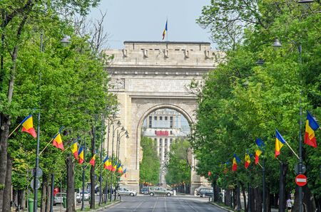 rumania: The Arch of Triumph (Arcul de Triumf) from Bucharest Romania, International Day with romanian flags, view from Kisseleff Avenue. Stock Photo