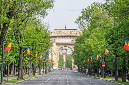 Der Triumphbogen (Arcul de Triumf) von Bukarest Rumänien, internationaler Tag mit rumänischen Flaggen, Ansicht von der Kisseleff Avenue.