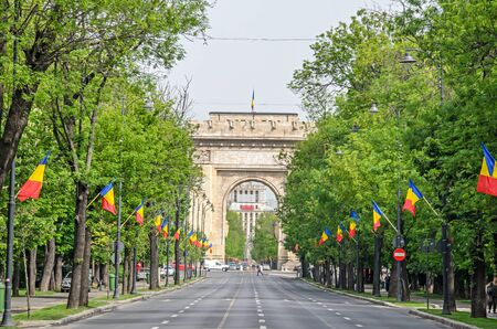The Arch of Triumph (Arcul de Triumf) from Bucharest Romania, International Day with romanian flags, view from Kisseleff Avenue. Banco de Imagens