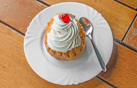 Savarin cake with cream and syrup, silver spoon, white plate on wood background.