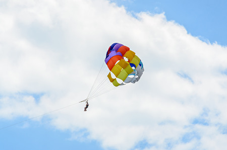Colored parasail wing in the blue clouds sky, Parasailing also known as parascending or parakiting.